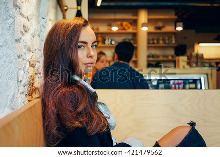 Portrait of a young attractive woman with beautiful chestnut hair who is sitting in a coffee shop while waiting for her morning coffee - stock photo