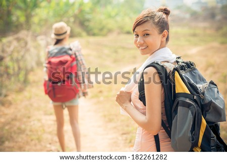 Portrait of a young backpacker with rucksack on the foreground while her friend standing on the background  - stock photo