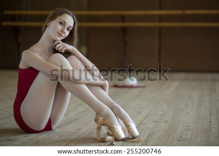 Portrait of a young ballerina sitting on the floor in a dance class. The model looks at the camera. - stock photo