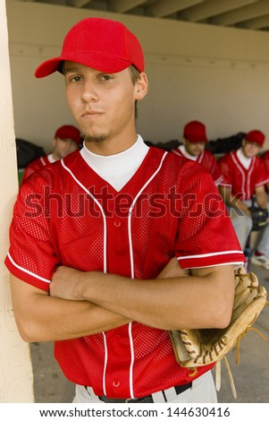 Portrait of a young baseball player with teammates sitting in dugout in background - stock photo