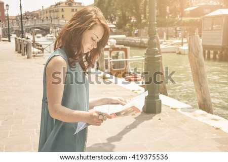 Portrait of a Young,  beautiful and caucasian woman that looks the map of a city,on Holiday - lifestyle,people and Holiday concept - stock photo