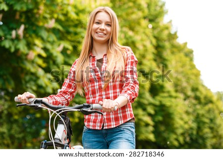 Portrait of a young beautiful blond girl standing near her mountain bicycle posing and smiling ,wearing a red checkered shirt  in a green park - stock photo