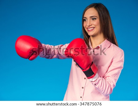 Portrait of a young beautiful business woman with boxing glove on hand on blue background - stock photo