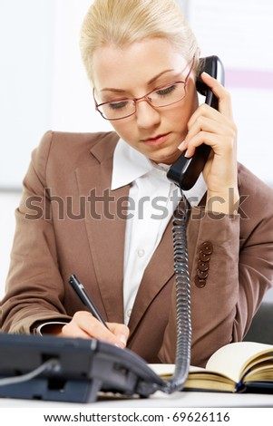 Portrait of a young beautiful businesswoman talking on the phone - stock photo