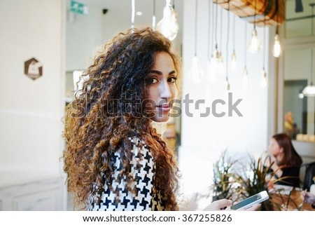 Portrait of a young beautiful businesswoman with long curly hair sending text message from her digital smart-phone in coffee-shop - stock photo