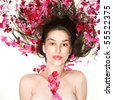 Portrait of a young, beautiful caucasian woman with petals of flowers over her body - stock photo
