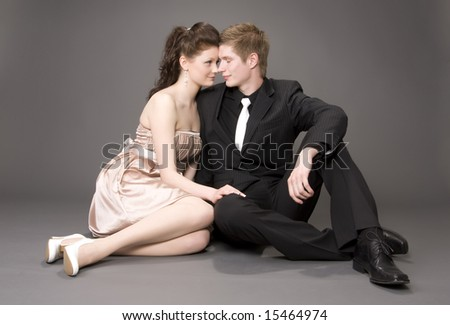 Portrait of a young beautiful couple on gray background