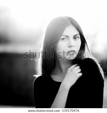 portrait of a young beautiful dark-haired woman in black and white - stock photo