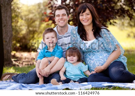 Portrait of a young beautiful family with pregnant mother - stock photo