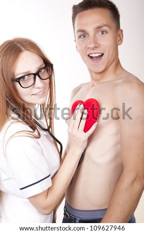 Portrait of a young beautiful female doctor checking patients heart. - stock photo