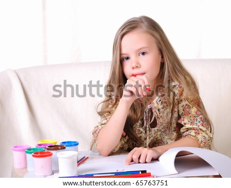 Portrait of a young beautiful girl. A girl is engaged in drawing - stock photo
