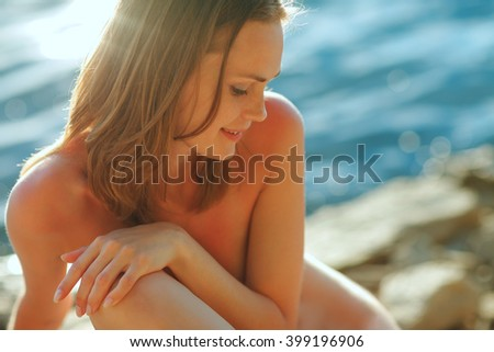 Portrait of a young beautiful girl in sunset light, with water in the background
