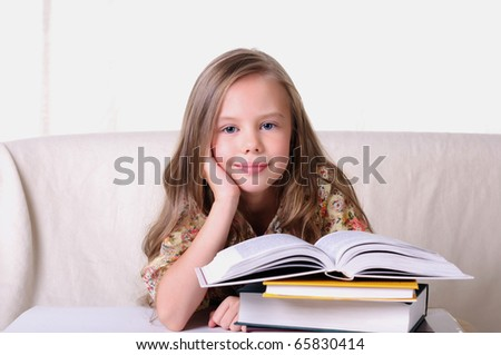 Portrait of a young beautiful girl. The girl is studying various textbooks.