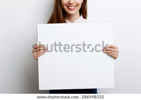 Portrait of a young beautiful girl with long brown hair wearing pink cotton blouse, standing smiling behind a square copy space in her hands, on a white background - stock photo
