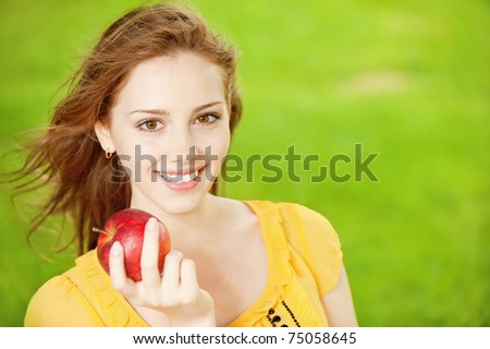 Portrait of a young beautiful girl with red apple on a background of green nature