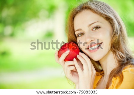 Portrait of a young beautiful girl with red apple on a background of green nature - stock photo