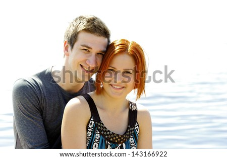 Portrait of a young beautiful happy couple outside on the lake shore hugging and smiling