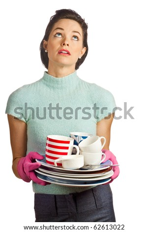 Portrait of a young beautiful housewife holding a pile of dirty dishes and looking fed up. Isolated over white. - stock photo