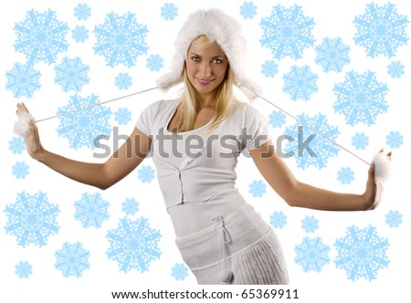 portrait of a young beautiful model in white winter dress with a nice fur hat