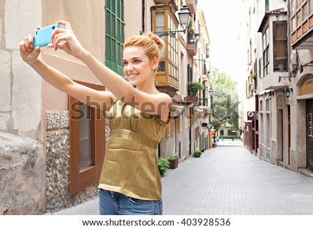 Portrait of a young beautiful tourist woman holding a smart phone device to take selfies in picturesque street on holiday, smiling and posing outdoors. Girl using technology networking, city exterior. - stock photo
