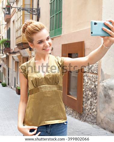 Portrait of a young beautiful tourist woman holding up using smart phone to take selfies in picturesque street on holiday, smiling and posing outdoors. Girl using technology networking, city exterior.