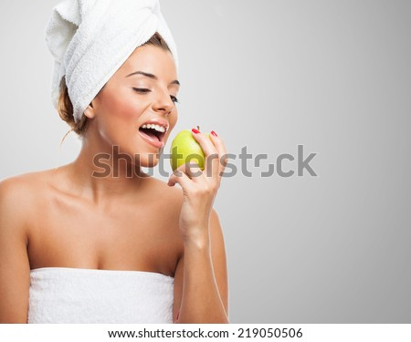 portrait of a young beautiful woman eating an apple after a bath - stock photo