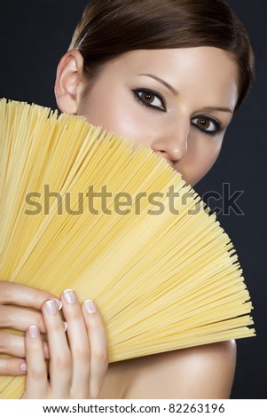 Portrait of a young beautiful woman holding a fan of spaghetti in front of her face with both hands