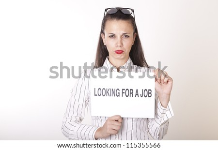 Portrait of a young beautiful woman holding a sign looking for a job.