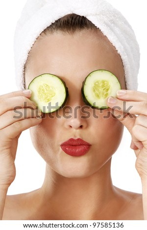 Portrait of a young beautiful woman holding cucumber slices on her eyes. - stock photo