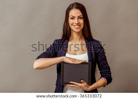 Portrait of a young beautiful woman in blue jacket and white shirt, showing a blank black screen tablet computer, smiling, looking at camera, on a gray background - stock photo