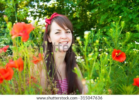 Portrait of a young beautiful woman in nature on a sunny summer day - stock photo