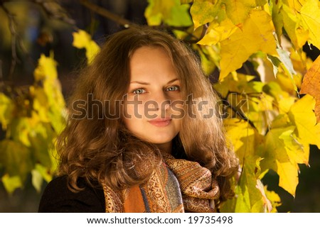 Portrait of a young beautiful woman in the autumn park