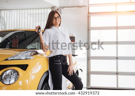Portrait of a young beautiful woman looking at the camera at the car showing keys. - stock photo