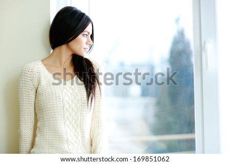 Portrait of a young beautiful woman looking at window - stock photo