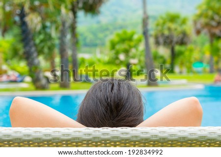 Portrait of a young beautiful woman lying on against the pool on the sun loungers. view from the back