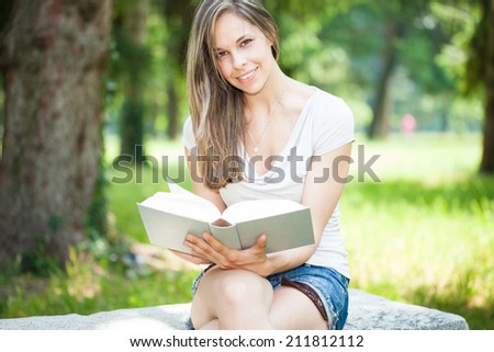 Portrait of a young beautiful woman reading a book in the park