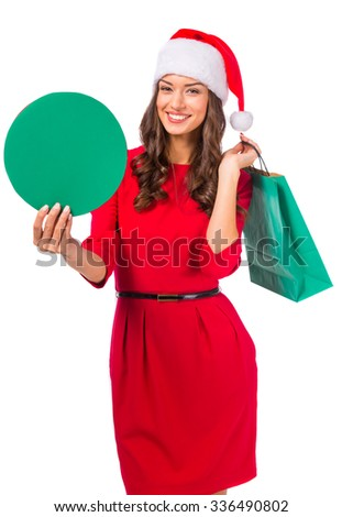 Portrait of a young beautiful woman with a Christmas hat on her head, holding shopping bags Christmas Sale. Isolated on white background - stock photo