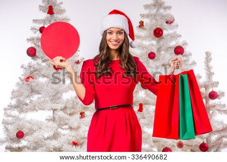 Portrait of a young beautiful woman with a Christmas hat on his head. Christmas Sale. Background Christmas tree - stock photo