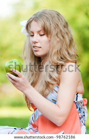Portrait of a young beautiful woman with green apple at park