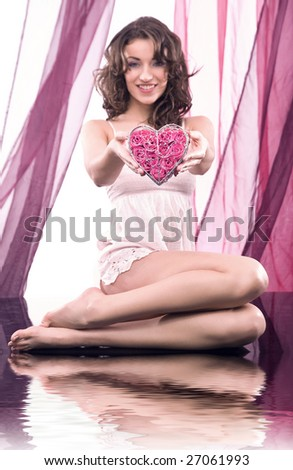 Portrait of a young beauty in spa holding a heart of roses - stock photo