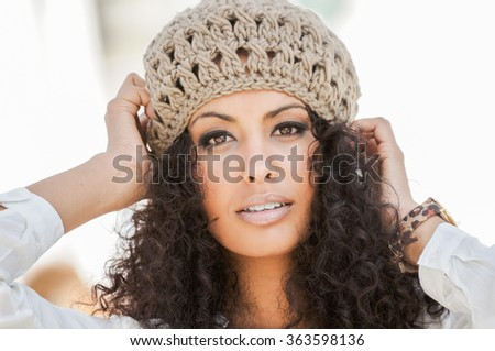 Portrait of a young black woman, afro hairstyle, in urban background, girl wearing wool cap - stock photo