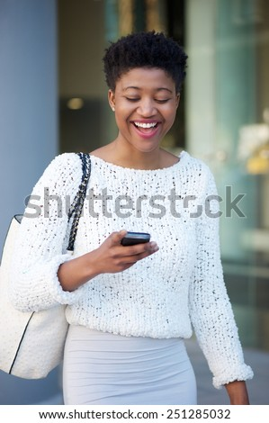 Portrait of a young black woman laughing and reading text message on mobile phone - stock photo