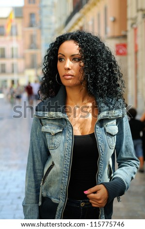Portrait of a young black woman, model of fashion in urban background with denim jacket - stock photo