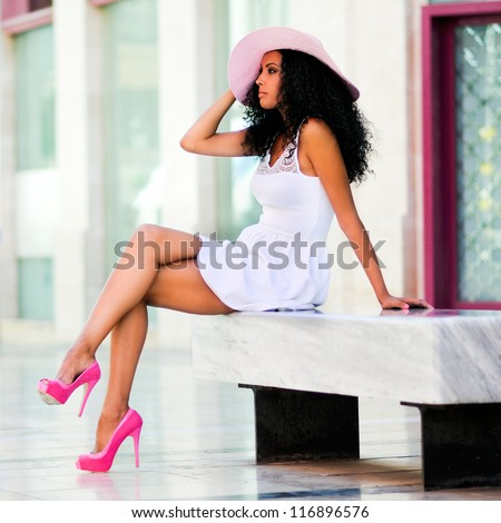Portrait of a young black woman, model of fashion wearing dress and sun hat, with afro hairstyle in urban background - stock photo