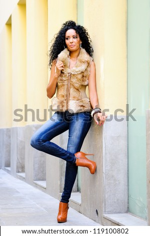 Portrait of a young black woman, model of fashion wearing fur vest and jeans - stock photo