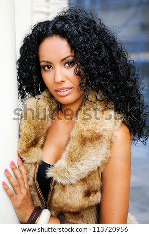 Portrait of a young black woman, model of fashion, wearing fur vest, with afro hairstyle in urban background
