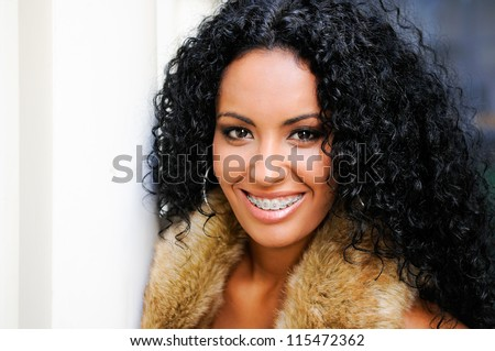 Portrait of a young black woman, model of fashion, wearing fur vest, with braces - stock photo