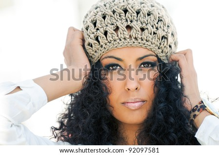 Portrait of a young black woman wearing a wool cap - stock photo