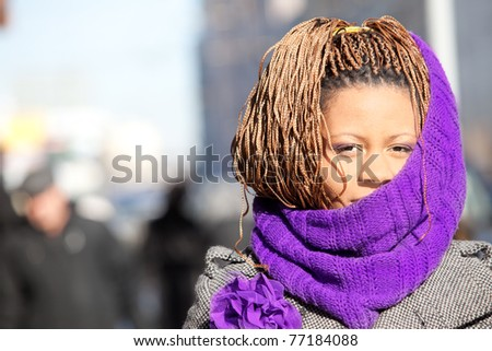 Portrait of a young black woman with purple scarf on the street