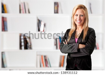 Portrait of a young blond business woman with her arms crossed - stock photo